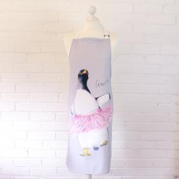 An apron featuring a gentoo penguin wearing a pink tutu